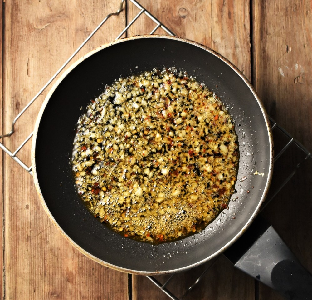 Spices with oil in frying pan.