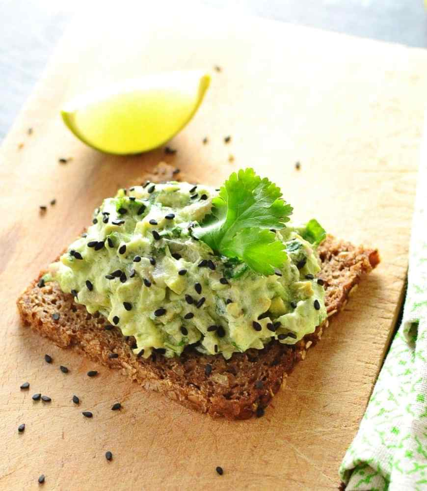 Avocado mixture with cilantro leaf on dark bread with lime wedge in background on light wooden cutting board.