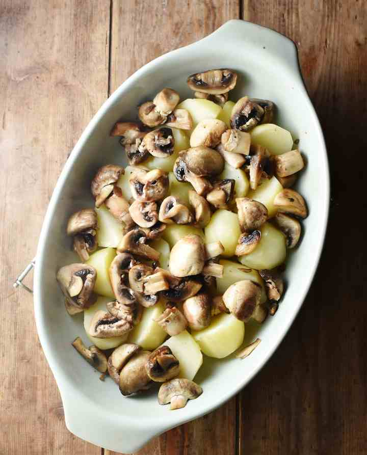 Potato pieces and chopped mushrooms in oval dish.