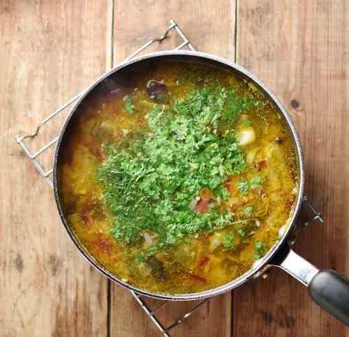 Soup with fresh herbs inside large pot.