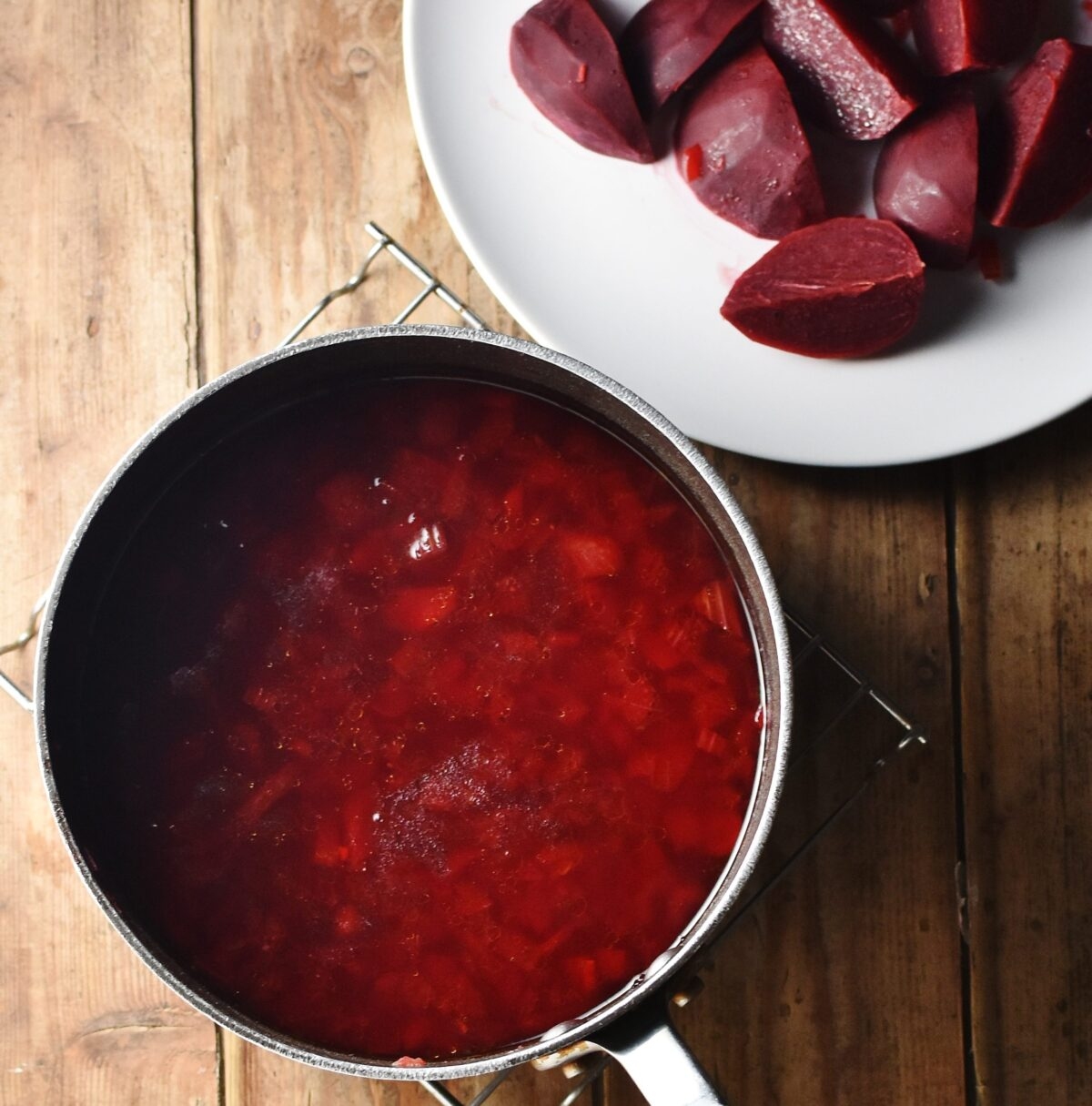 Borscht soup in large pot and quartered beets on white plate in top right corner.