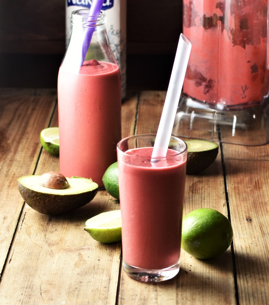 Side view of pink avocado smoothie in glass with straw, limes, avocado, smoothie in bottle and in blender in background.