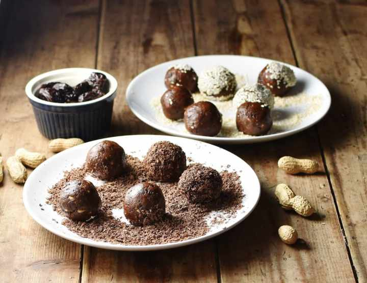 Side view of energy balls on 2 white plates coated in chocolate and seeds, with peanuts and prunes in blue container in background.