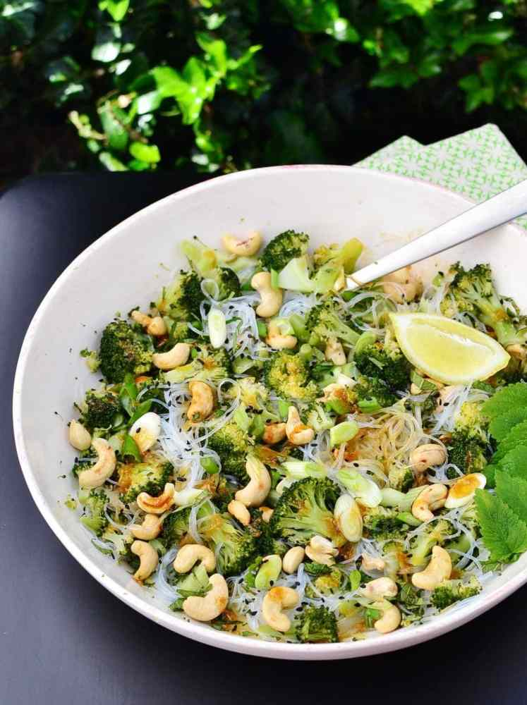 Close-up view of broccoli bean thread salad with cashews, mint leaves, lemon wedge and spoon inside white bowl.
