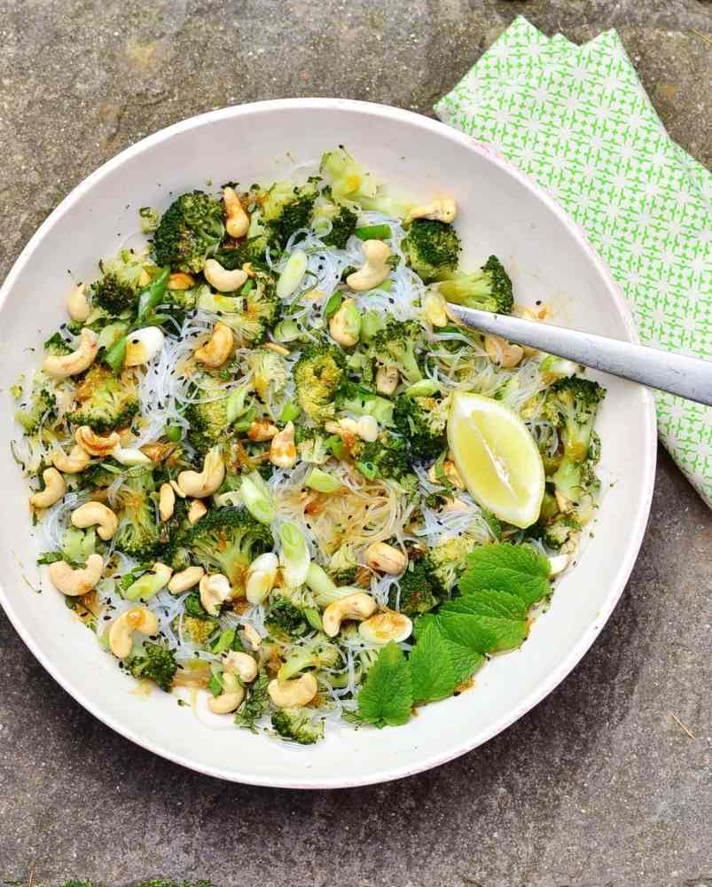 Asian noodle salad with broccoli, cashews and fork in white bowl with green cloth.