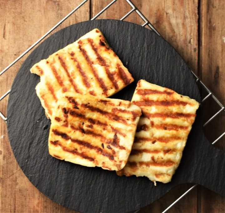 3 slices of grilled halloumi cheese on top of black platter.