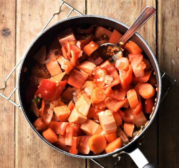 Chopped sweet potato, carrot and red pepper in large pot with spoon.