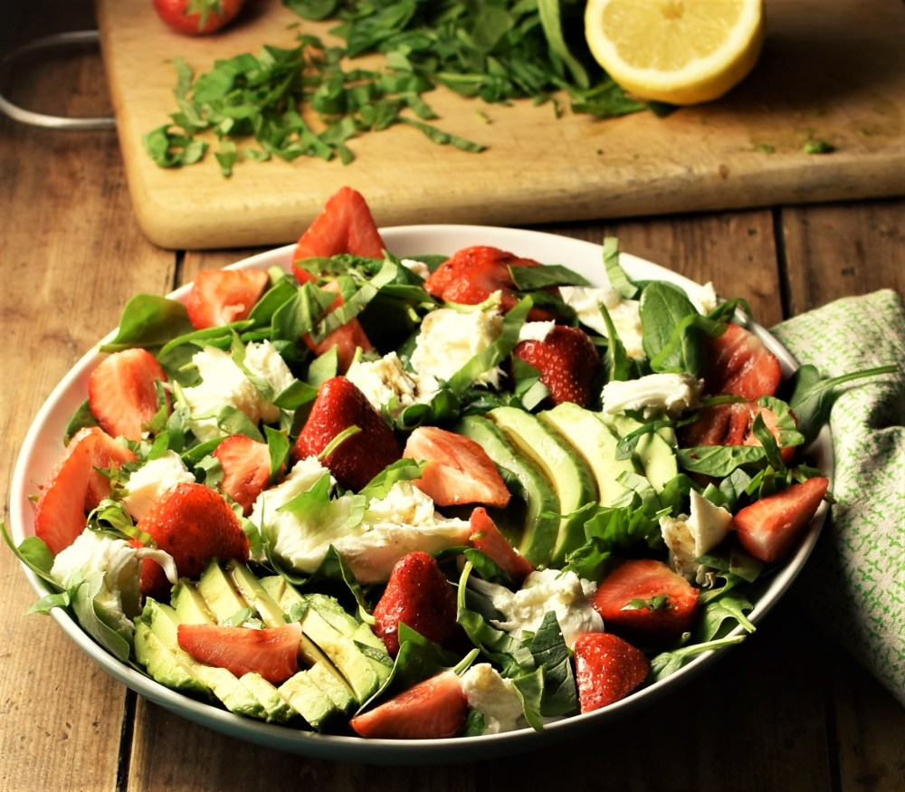 Avocado, spinach, strawberry and mozzarella salad on white plate with lemon and chopped spinach in background.