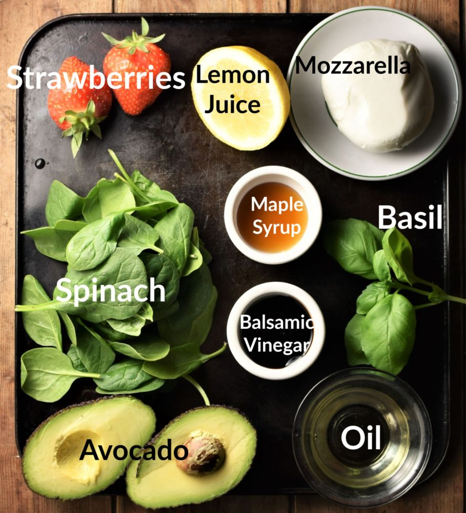 Strawberry and spinach salad ingredients in individual dishes.