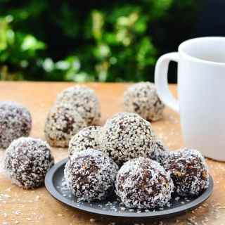 Side view of chocolate energy balls on black plate with white cup on wooden table.