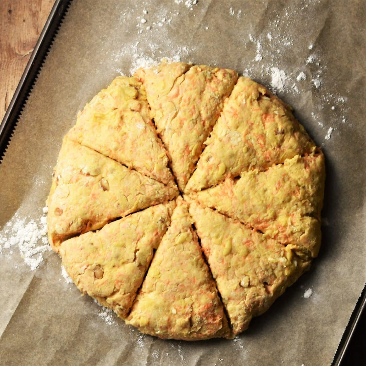 Carrot scones dough flattened and cut into 6 triangles on top of parchment paper.