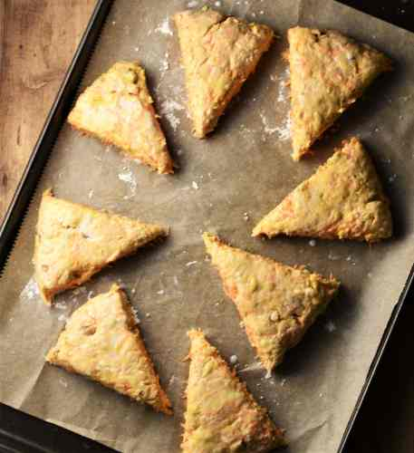 8 unbaked triangular carrot scones on top of large baking sheet lined with parchment paper.