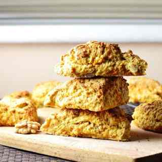 Triangular carrot scones with walnuts scattered in wooden cutting board.