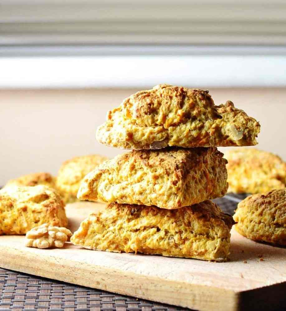 Side view of stack of 3 carrot scones with more scones in background on top of wooden board.