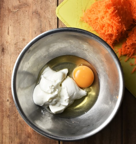Egg and yogurt in metal bowl, with finely grated carrot on top of yellow board in top right corner.