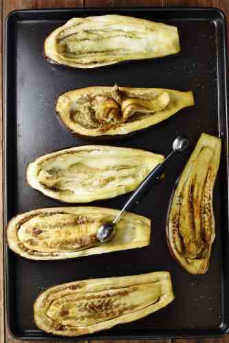 6 roasted eggplant halves with melon baller.