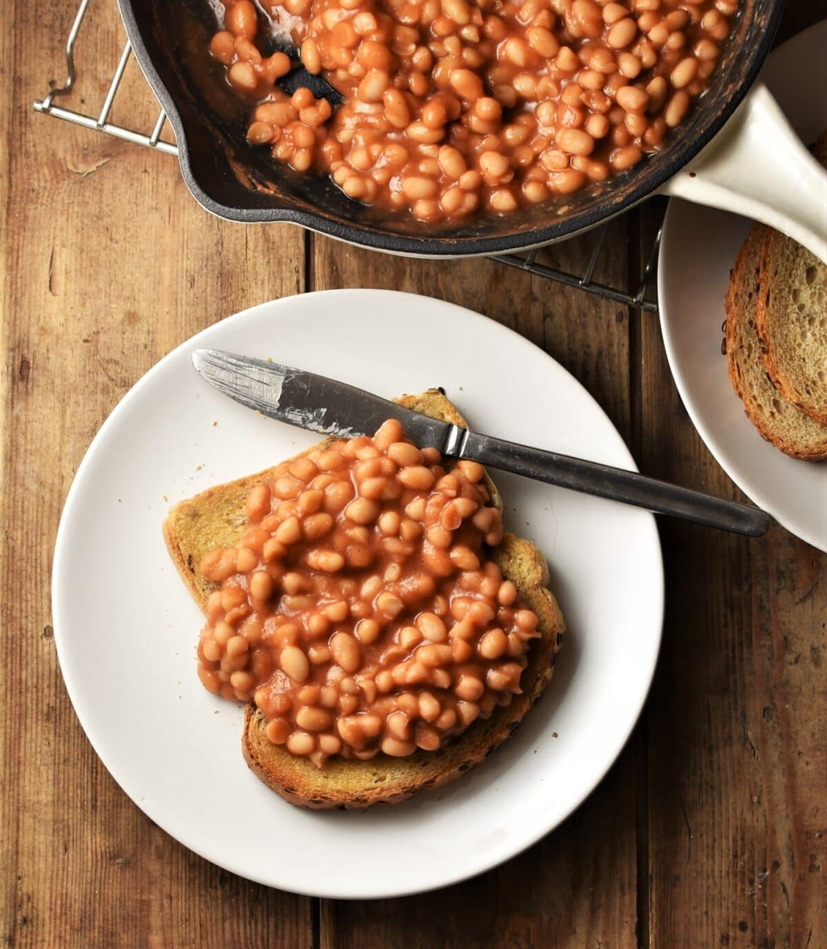 Baked beans on top of toast on white plate with knife, with beans in skillet in background.