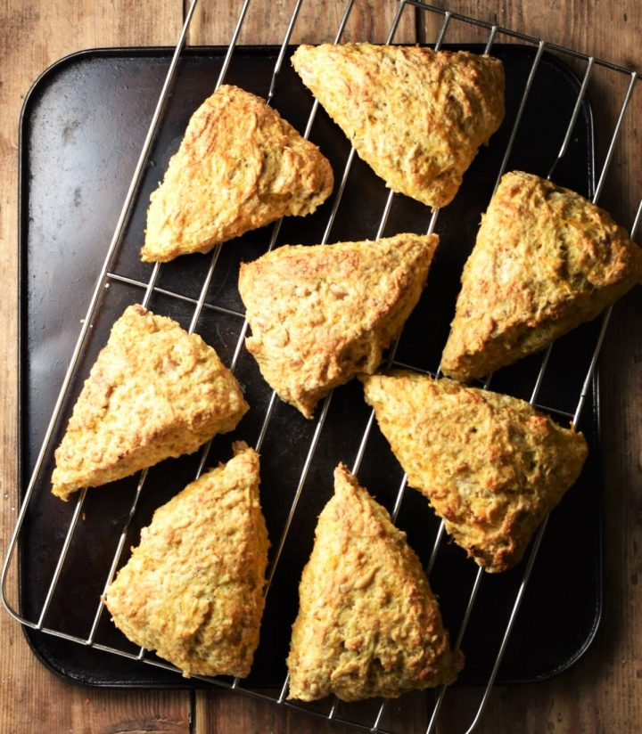 8 baked scones on top of rack on black tray.