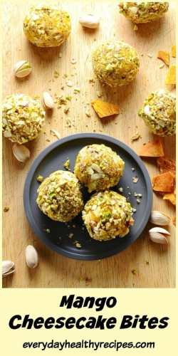 Top down view of mini cheesecake balls on small grey plate on top of wooden table with pistachios and dried mango pieces.