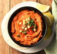 Top down view of red pepper hummus in black bowl on top of plate with tortillas and lemon wedges.