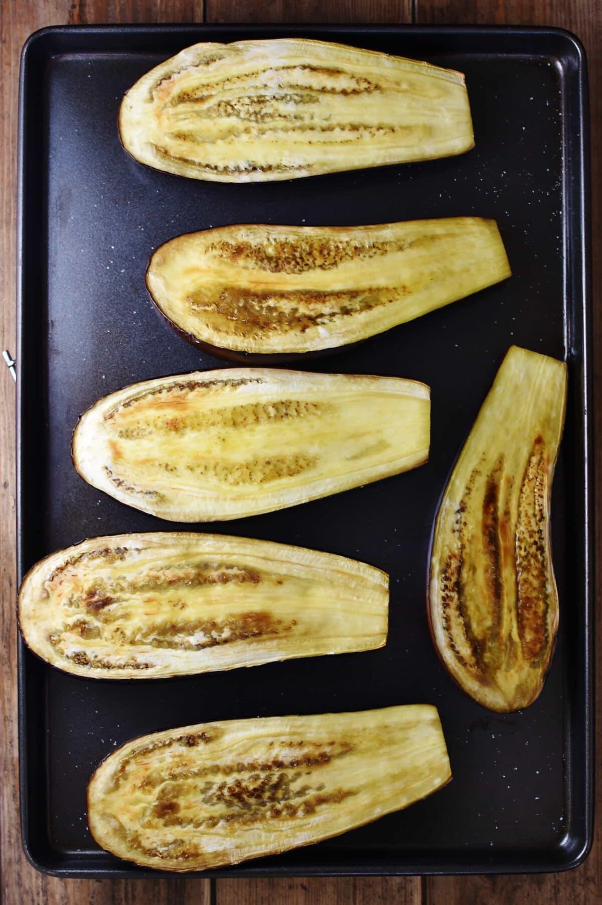 6 roasted eggplant halves on large oven sheet.