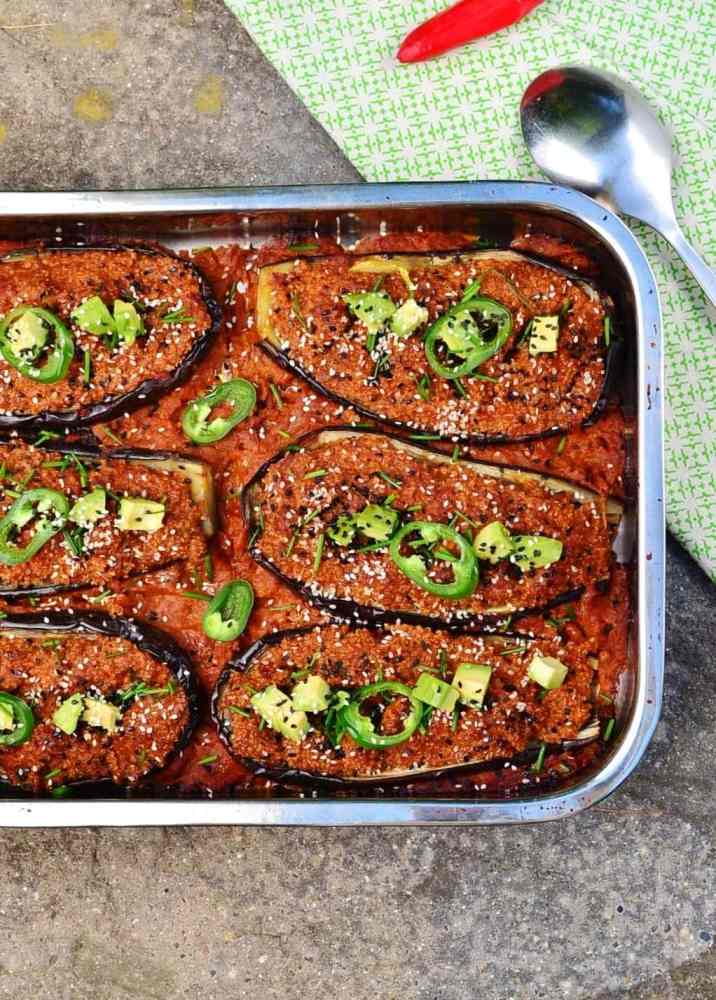 Top down view of stuffed eggplant in tomato sauce in rectangular metal dish with spoon and red chilli on green cloth in top right.