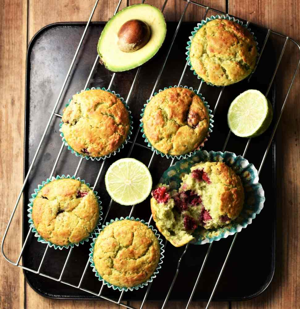 Avocado muffins with limes and fresh avocado on top of rack.