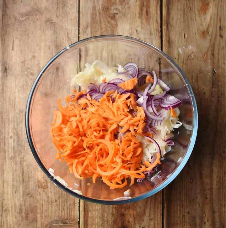 Spiralized carrot, sliced red onion and sauerkraut in mixing bowl.