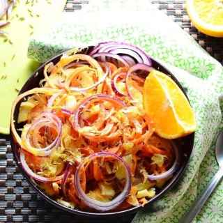 Top down view of sauerkraut carrot salad in purple bowl with orange, green cloth and partial view of yellow board.