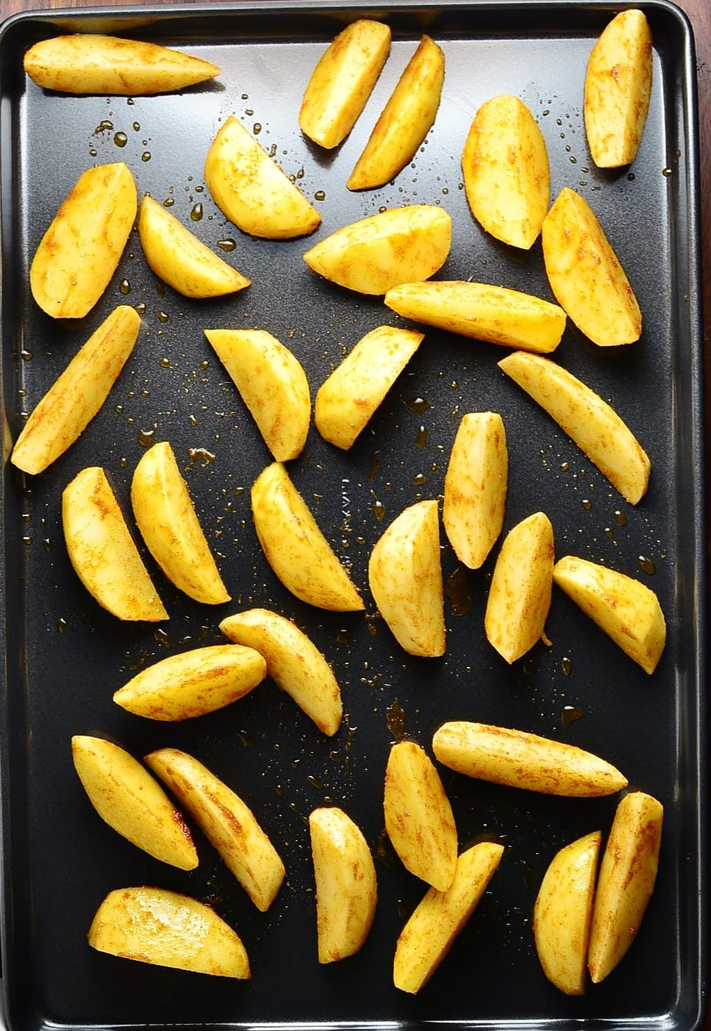 Top down view of potato wedges on top of tray.