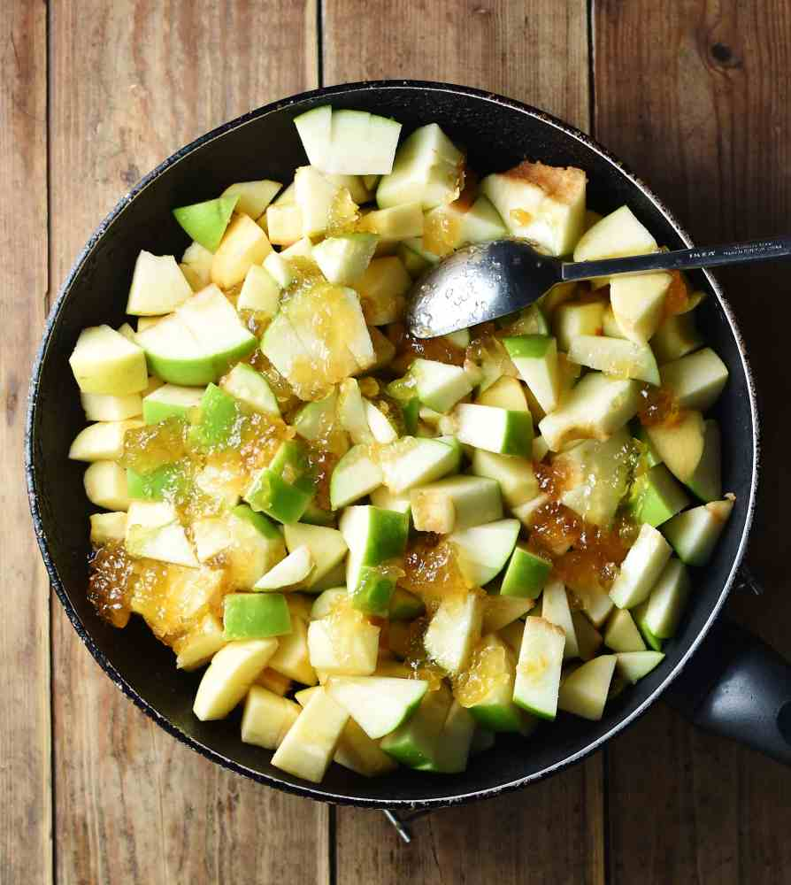 Apple pieces with jam and spoon inside large pan.