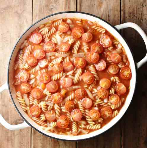 Fussili pasta with tomatoes in large white shallow casserole dish.