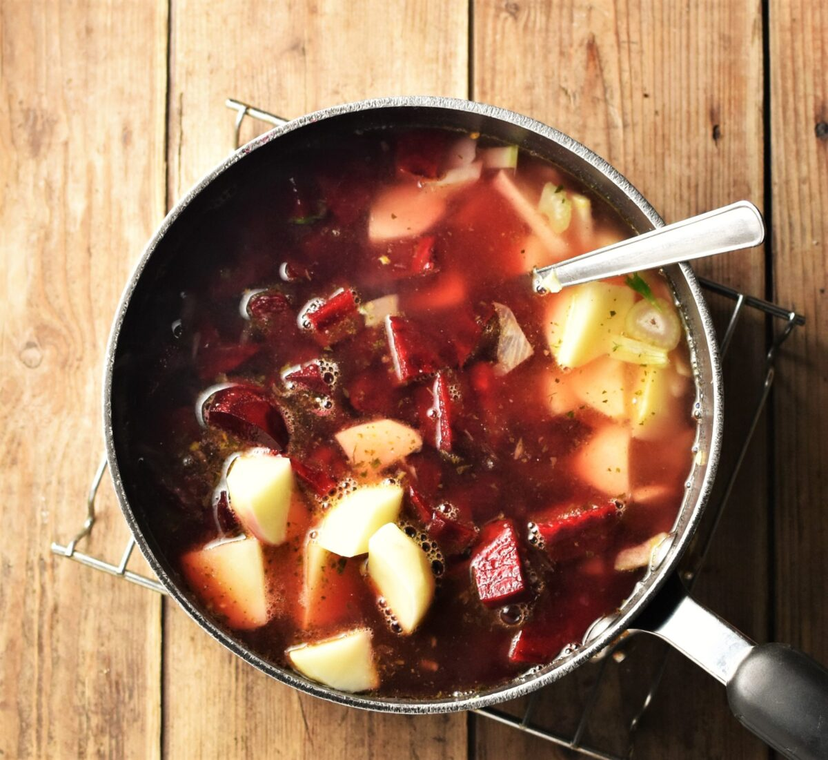Chopped beetroot, potatoes and stock in large pot with spoon.