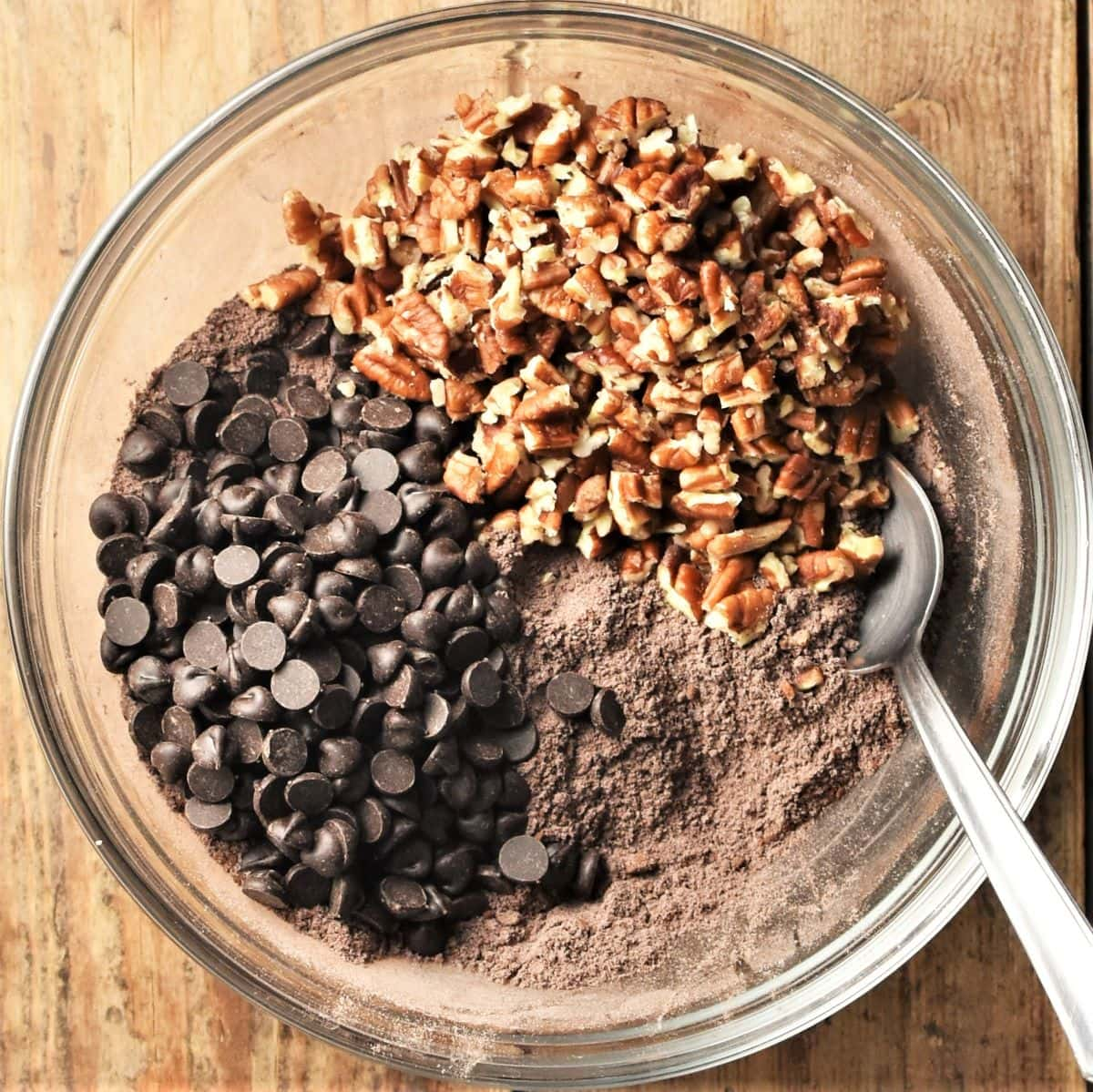 Cocoa mixture with chocolate chips and chopped pecans in mixing bowl with spoon.