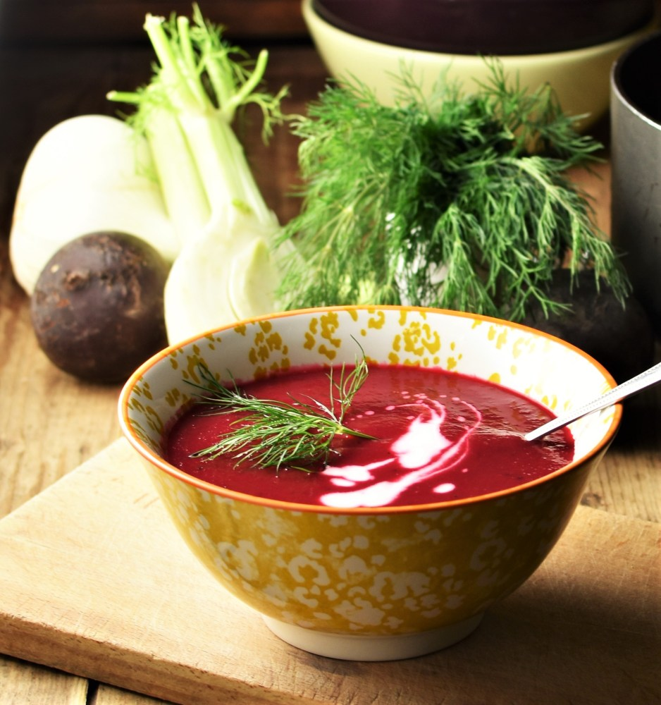 Side view of creamy beet soup with dill and yogurt in yellow patterned bowl with spoon, dill, fennel and bowls in background.