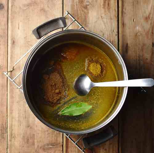 Spices with bay leaf and oil in pot with spoon.