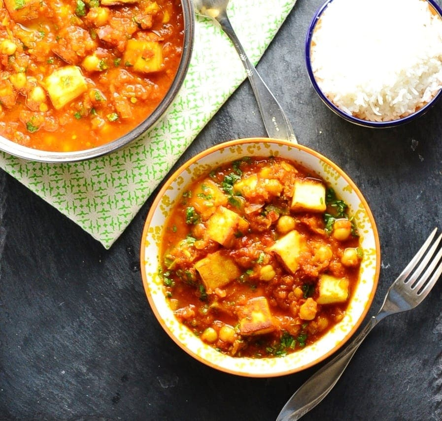 Top down view of vegetarian curry with paneer in white-and yellow bowl and saucepan, with fork, green cloth and bowl of rice.