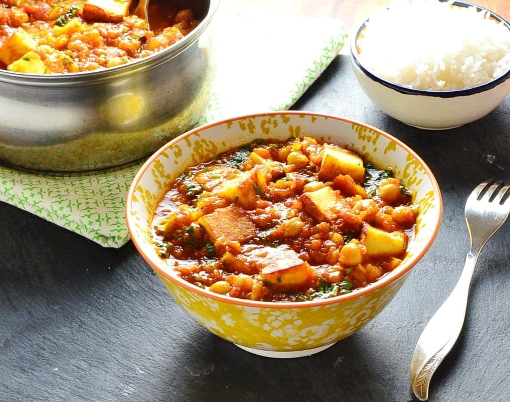 Vegetarian curry with paneer in white-and-yellow bowl with saucepan and bowl of rice in background and fork to right.
