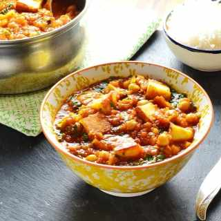 Vegetable curry with paneerin white-and-yellow bowl with saucepan and bowl of rice in background and fork to right.