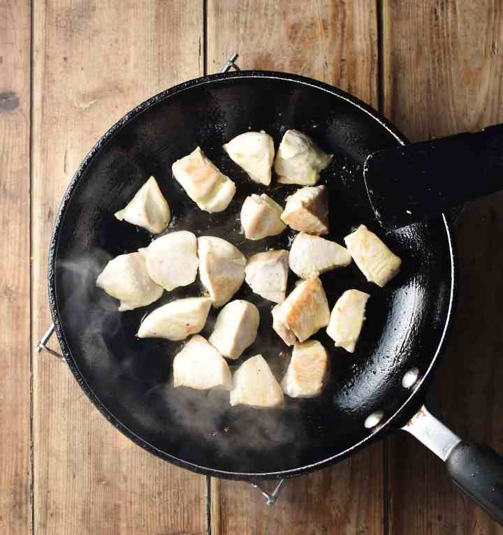 Chicken pieces in large frying pan with black spatula.