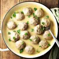 Meatballs in white sauce with spoon in large shallow dish.