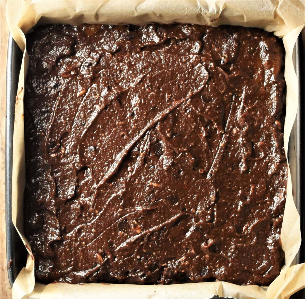 Unbaked brownies cake in square pan.