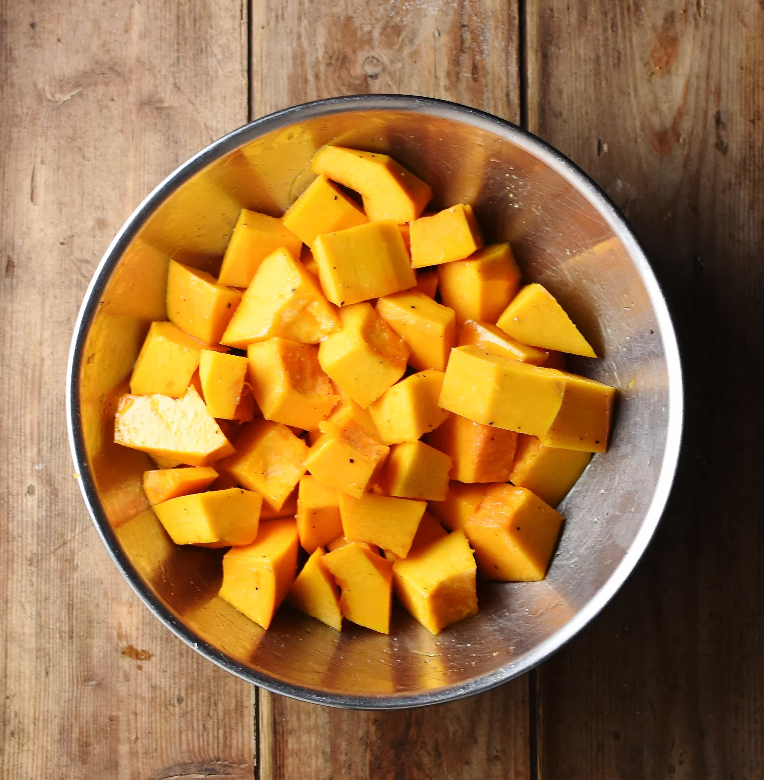Pumpkin cubes in large metal bowl.