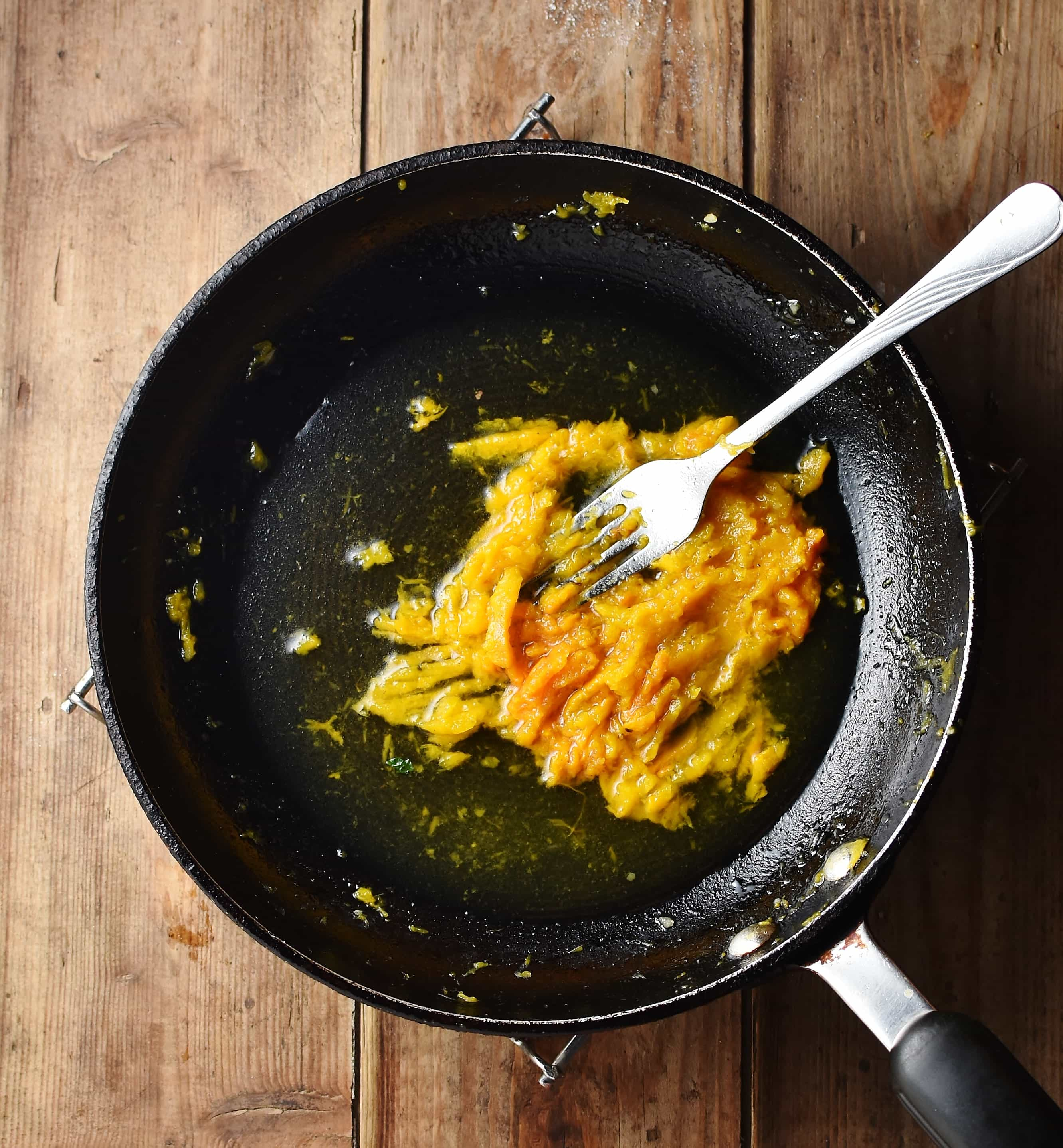 Mashed pumpkin with water and fork in black pan.