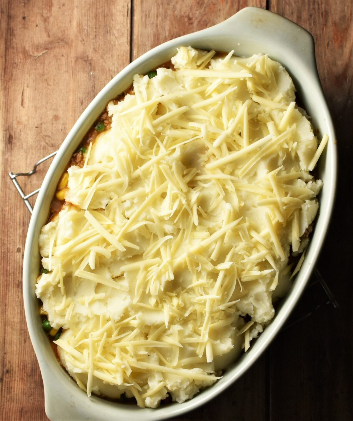 Pie topped with potato mash and grated cheese in green oval dish.