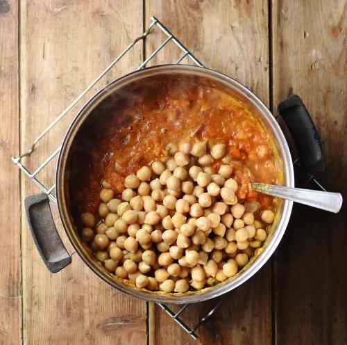 Chickpeas and tomato sauce in pot with spoon.