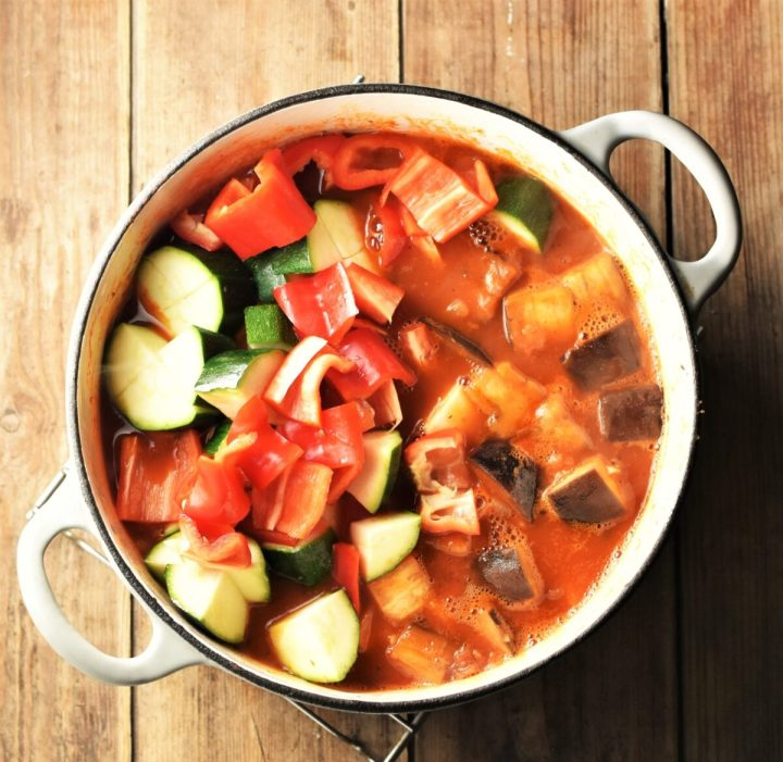 Chunky vegetables in tomato sauce in large white pot.