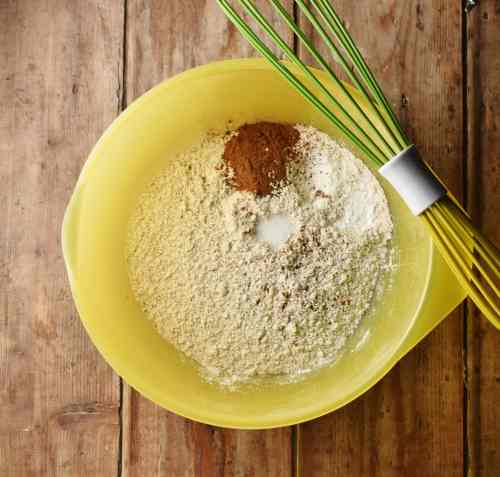 Flour and spice mixture in large yellow bowl with green whisk.