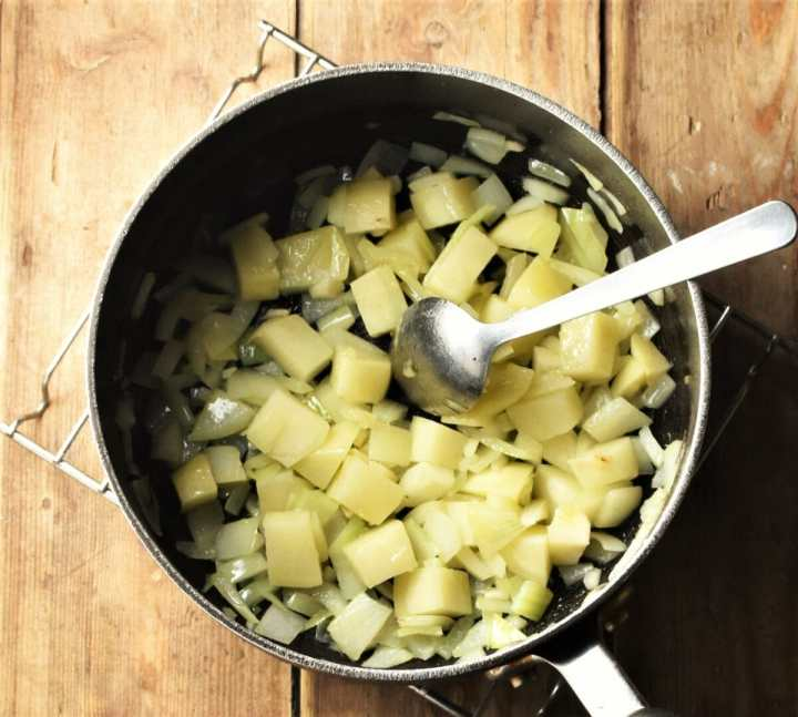 Cubed potatoes and chopped onion in large pot with spoon.
