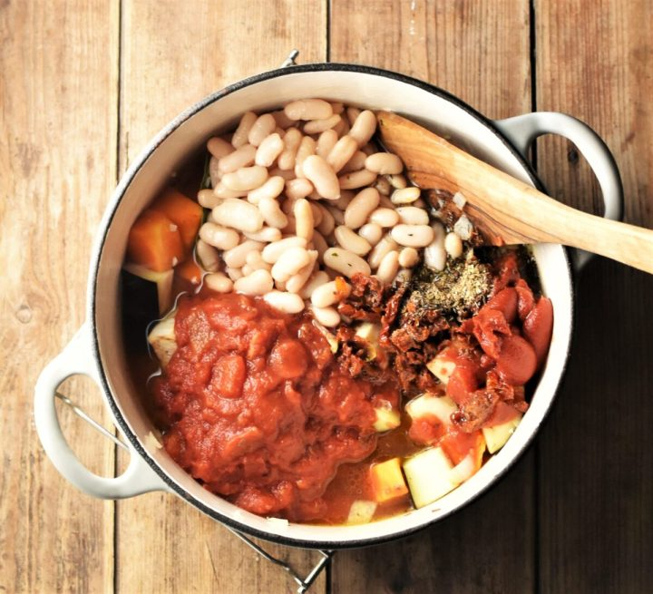 Chopped tomatoes, white beans, tomato paste and wooden spatula in large white pot.